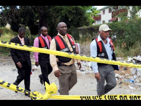 Police investigators at a murder scene on Trafalgar Road in St Andrew in June 2012.