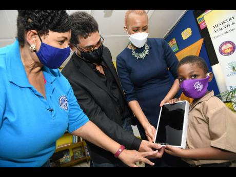 Douglas Augustine Ekele Mukwelle (right), shows his tablet to Reece King (second left), of RMP and Associates Limited, Fayval Williams (right) Minister of Education, Youth and Information and Greta Bogues, CEO of The Private Sector Organisation of Jamaica