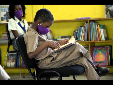 Douglas Augustine Ekele Mukwelle, reads a book while waiting on his tablet, donated by RMP and Associates Limited at John Mills Primary and Infant School on January 22.