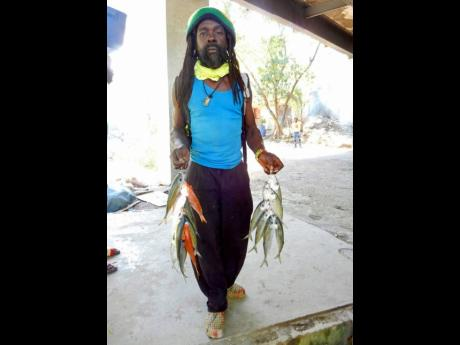 A fisherman with two strings of fish.