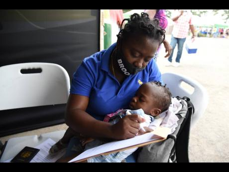 Peta-Gay Harris fills out a passport form for her daughter, Raine-Alexis, during a visit by the mobile unit of the Passport, Immigration, and Citizenship Agency in Spanish Town, St Catherine, on Saturday.