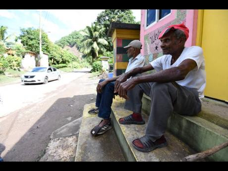 Herman Latouche (foreground) and Herman Walters of Broadgate, St Mary, lament the slow pace of the road rehabilitation.