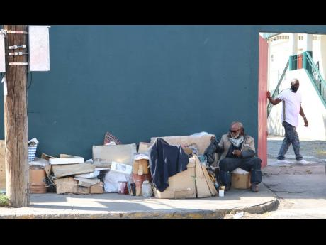 A homeless man sitting outside the gates of Palace Amusement's Carib 5 cinema in Cross Roads, St Andrew, with all his worldy possessions yesterday. At least six homeless men were attcked on the streets of the Corporate Area on Sunday night.
