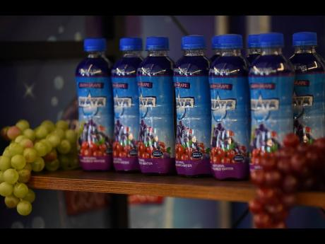 iCool juice drinks made and flavoured WATA drinks, both made by Jamaican manufacturers, are displayed. With the policy-mandated movement towards less sugar in drinks, there is expectation that regular drinks and flavuored waters could end up in direct comp