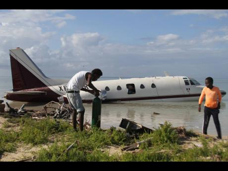 Residents of Rocky Point, Clarendon, scavenge for equipment and paraphernalia from a plane that crash-landed on Saturday, January 23.
