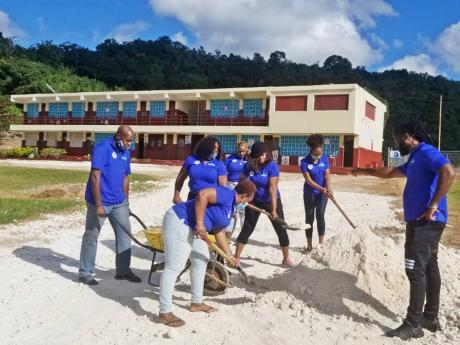 Members of the Kiwanis Club of Charlton-Alexandria spreading marl on the driveway at the Aboukir Primary School before it was paved.
