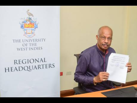 Professor Sir Hilary Beckles, vice-chancellor of The UWI, holds up a copy of the MOU for the Centre for Excellence for Oceanography and the Blue Economy.