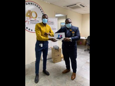 Daniel Jarrett (left), projects officer at the Grace and Staff Community Foundation, presents 20 tablets to United Student Movement (USM) president, Ruel Haye. The tablets will be distributed to students at the Northern Caribbean University who are in need