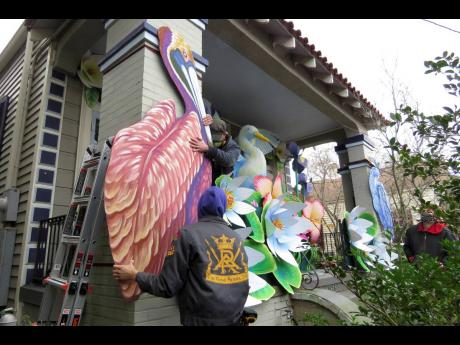 Parade float workers Travis Keene (left) and Joey Mercer position a pelican while fellow crew member Chelsea Kamm (right) looks on, as the two decorate a house in New Orleans.