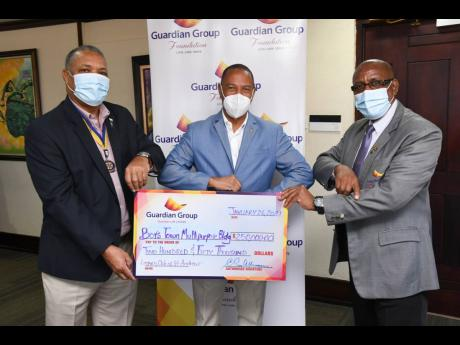 Rotary Club of St Andrew President Audley Deidrick (left) joins with past president, Eugene Folkes (centre), to accept a Guardian Group Foundation donation from insurance adviser, Clinton McClennon, Guardian Life Limited. The Rotary Club will use the funds