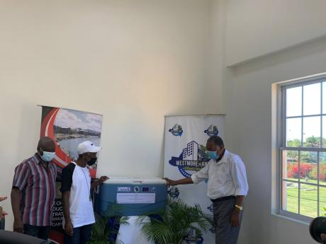 From Left: Oyster farmers  Sherwin Pinnock and Demetrius Samuels receive equipment for their newly established oyster farm from the Westmoreland Municipal Corporation. Doing the handover is Mayor of Savanna-la-Mar Bertel Moore.
