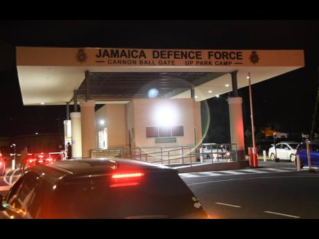 Vehicles enter and exit the Jamaica Defence Force headquarters at the Cannon Ball Gate on Camp Road, Kingston, on Wednesday night. A lieutenant enmeshed in a sex scandal has resigned, the army revealed.