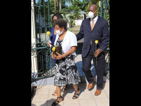 Mavis Beckford, who was married to advertising icon Gurney Beckford for 57 years, is escorted by daughter Andrea Wray and son Gavin Beckford as she carries the urn with her late husband's remains to yesterday's thanksgiving service at the Sts Peter and