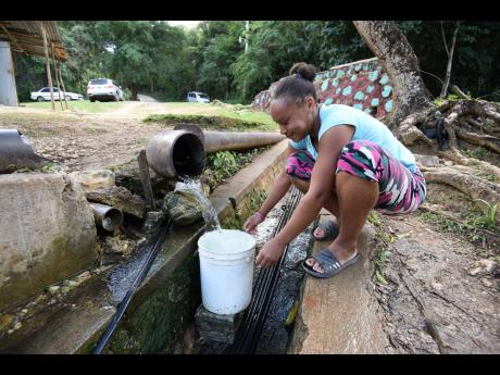 Angellina Simmonds catching water from the Crawl Pass spring in Bois Content, Clarendon, on Thursday. The residents, who have to pay for water trucked into the community, are bemoaning the challenge they have accessing water for domestic and farming purpos