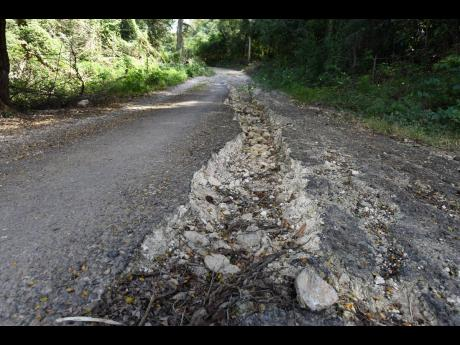 A section of the roadway in Bois Content, Clarendon, which residents say their member of parliament has told them will not be repaired until pipes have been laid. They have received no timeline for either.