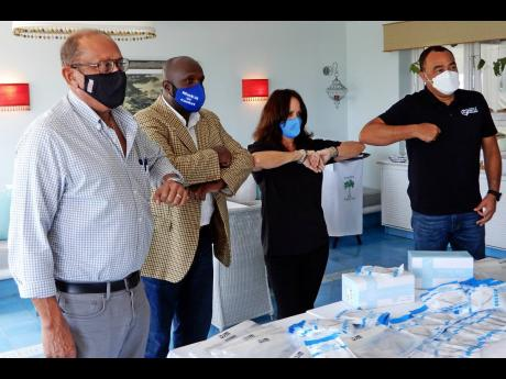 From left: Howard Mitchell, NHF chairman; Delroy Morgan, St Ann's Bay Regional Hospital CEO; Alex Ghisays, PR director, ITF, and Health Minister Dr Christopher Tufton touching elbows, with some of the PPE on display.