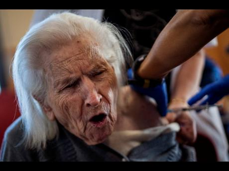 A nurse administers the Pfizer-BioNTech COVID-19 vaccine to a resident at the Icaria nursing home in Barcelona, Spain, on Tuesday. Spain's top coronavirus expert suggests that the coronavirus vaccine manufactured by AstraZeneca should be administered to yo