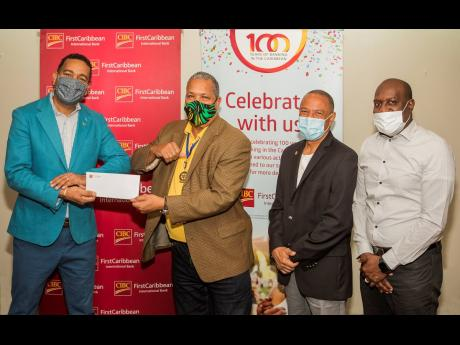 Nigel Holness (left), managing director, CIBC FirstCaribbean International Bank, presents a cheque to Rotary President Audley Deidrick (second left). Looking on are  past presidents Eugene Folkes (second right)  and Wayne Strachan, in support of the Rotary