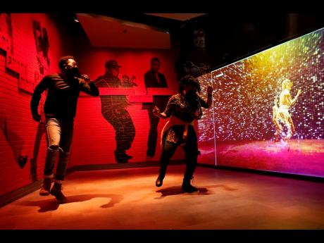 Armond Carter (left) of Atlanta and his mother, Latonya Carter, dance together in an exhibit at the National Museum of African American Music.