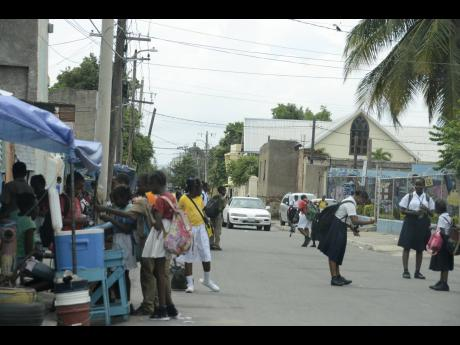 File  In this 2017 photo, students stop by a vendor to purchase snacks, sweet treats and juices on their way home from school in Southside, Kingston.