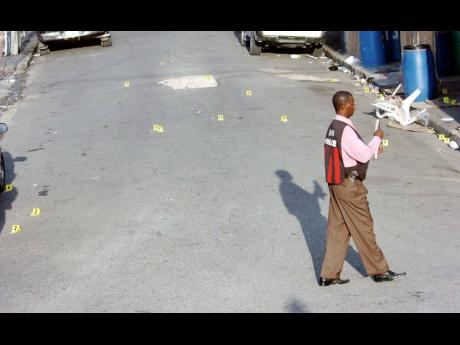 In this 2008 file photo. a policeman walks across 28 spent shell markers on Laws Street in downtown Kingston after a daring attack by gunmen in which 13 persons were injured. One person later died. The shooting was believed to be a result of a fued between