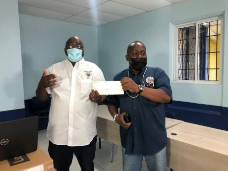 Acting Principal Wayne Robinson (left), accepts a cheque from Noel Brown on behalf of the Jamaica College Old Boys Association.