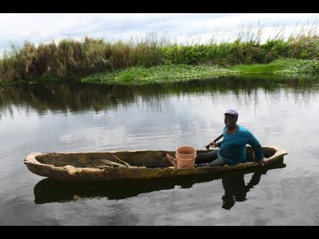 Fisherman Cleveland Watson in his boat on the Black River.