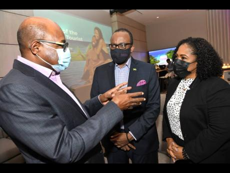From left: Minister of Tourism Edmund Bartlett and Donovan White, director of tourism, chat with Camile Glenister, deputy director of tourism, marketing, at the launch of Jamaica Tourist Board's Romance Microsite, wedding and honeymoon website.