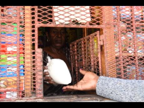 A shopkeeper in Kingston hands a bag of flour weighing two pounds to a customer on Tuesday. Jamaica Flour Mills, the main wholesaler of flour in the island, has increased prices by up to 14 per cent.