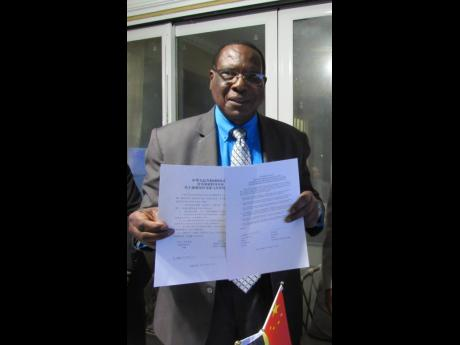 Mayor of Montego Bay, Leeroy Williams, proudly displays a signed copy of the MoU that established sister-city relations between Montego Bay and Zhuhai in China.