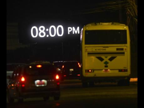 A Jamaica Urban Transit Company bus drives towards an automated billboard in the vicinity of the Portmore Mall in St Catherine on Tuesday night. Prime Minister Andrew Holness announced a tighter two-week national curfew set to begin at 8 p.m. today.