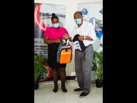 Mayor of Savanna-la-Mar Bertel Moore hands over a disaster preparedness kit to a participant in the Family Disaster Plan and Radio Quiz competitions staged by the Westmoreland Municipal Corporation under the Climate Change Adaptation and Risk Reduction Tec