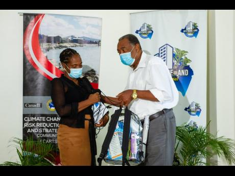 Seventeen participants of the Family Disaster Plan and Radio Quiz competitions staged by the Westmoreland Municipal Corporation received disaster preparedness kits recently. Here, Savanna-la-Mar Mayor Bertel Moore hands over one of the  kits to a participa