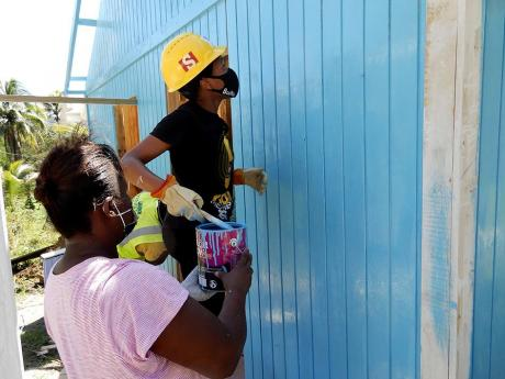 Two women combine efforts to complete the paint job on the new house for the Pink family in Fontabelle, St Mary, on Wednesday.
