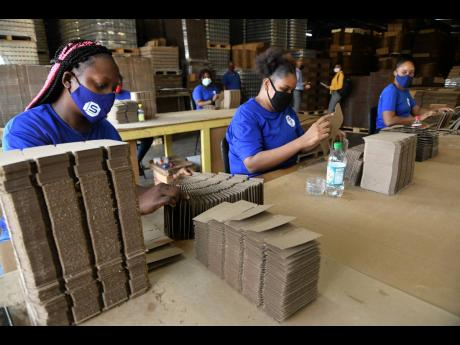 Workers sort hrough partitions on the factory floor at Sterling Packaging Limited in Kingston on February 8, 2021.