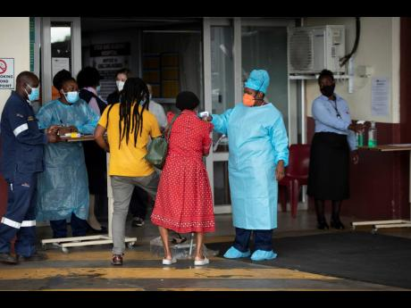 A health worker checks the temperature of an elderly patient at the emergency entrance of the Steve Biko Academic Hospital in Pretoria, South Africa, on Jan 11, 2021, which is battling an ever-increasing number of COVID-19 patients.