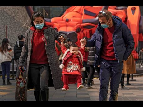A couple wearing face masks to help curb the spread of the coronavirus lift their child wearing a new year costume as they visit to the capital city's popular shopping mall during the first day of the Lunar New Year in Beijing.
