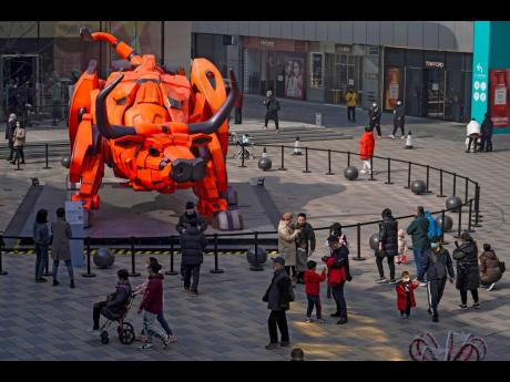 People wearing face mask to help curb the spread of the coronavirus gather near an ox statue on display at the capital city's popular shopping mall during the first day of the Lunar New Year, Year of the Ox, in Beijing.