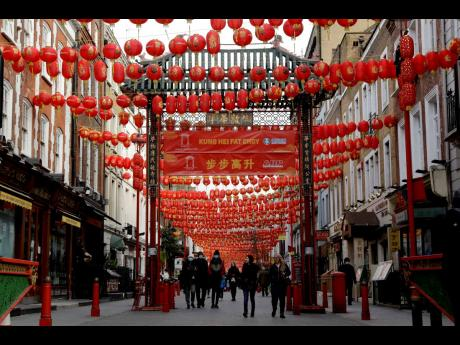 People walk beneath lanterns hung across the street to celebrate the Chinese Lunar New Year which marks the Year of the Ox, in the Chinatown district of central London, Friday, February 12, 2021.