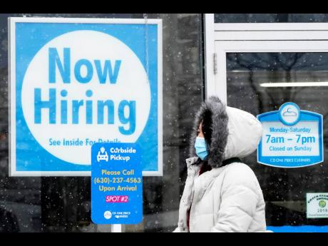 """In this February 6, 2021 file photo, a woman walks past a """"Now Hiring"""" sign displayed at a CD One Price Cleaners in Schaumburg, Illinois. In a stark sign of the economic inequality that has marked the pandemic recession and recovery, Americans as a w"""