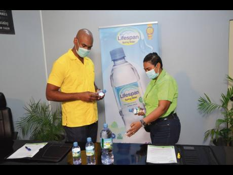 Newly minted Lifespan Spring Water medical spokesperson Dr Alfred Dawes (left) observes the retail sizes of the product with the company's CEO, Nayana Williams.