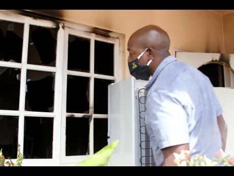Nathaniel Stewart/Photographer  Clarendon South Eastern Member of Parliament Pearnel Charles Jr examines the damage done to this home, which was firebombed in Lionel Town on Friday night. It is the third house in the community to be firebomded in two weeks
