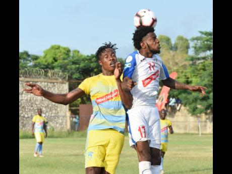 Portmore United's Tevin Shaw (right) heads the ball away while challenged by Waterhouse's Stephen Williams during their Jamaica Premier League match at the Spanish Town Prison Oval on Sunday, November 10, 2019.