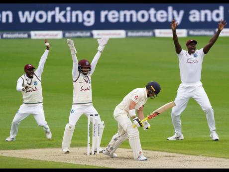 West Indies players appeal successfully for the wicket of England's Rory Burns (second right) during the first day of their second Test at Old Trafford in Manchester, England, on Thursday, July 16, 2020.