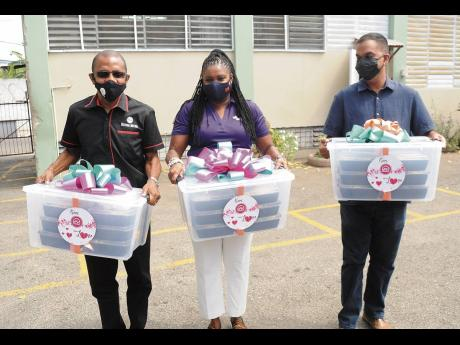 From left: Courtney Campbell, group president and CEO, Victoria Mutual; Clover Moore, assistant vice-president, group corporate affairs and communications; and Robert Lalah, assistant manager, group corporate affairs and communications, carry containers w
