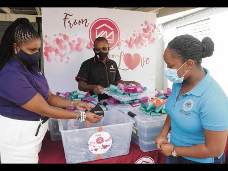 Victoria Mutual Group President Courtney Campbell (centre) looks on while Clover Moore (left) shows Hotiyana Brown, secretary to the Inspector of Poor, some of the masks that were also donated to the shelter.