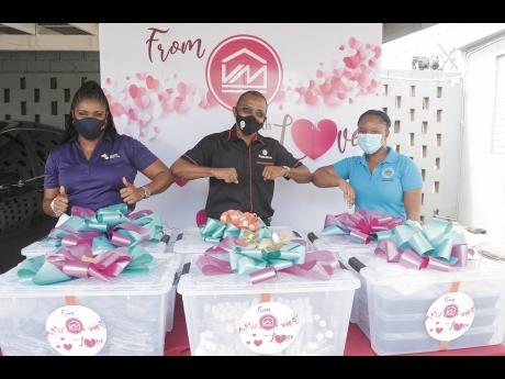 Clover Moore (left), assistant vice-president, group corporate affairs and communication, Victoria Mutual Group; Courtney Campbell, group president and CEO; and Hotiyana Brown, secretary to the Inspector of Poor, greet each other during the handover of the
