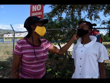 Beverly Smith fixes her daughter Brianna Jackson's mask as they await transportation outside Mona Heights Primary School yesterday.