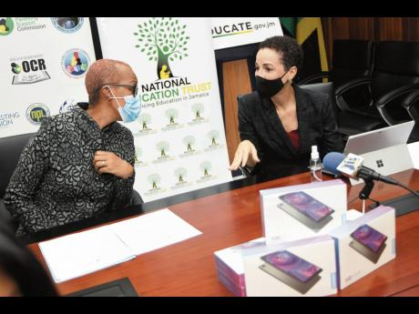 Senator Kamina Johnson Smith (right), minister of foreign affairs and foreign trade, talks with Fayval Williams, minister of education, youth and information,during a ceremony for the handover of tablets to the ministry by the Jamaican Consulate in New Yor