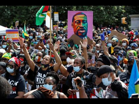 People inspired by a speaker raise their hands during a Caribbean-led Black Lives Matter rally at Brooklyn's Grand Army Plaza in New York, on Sunday, June 14, 2020.